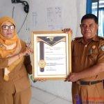 Sekretaris BKPSDM Busel (Kanan) saat menunjukkan Piagam Penghargaan yang diterima dari BKN