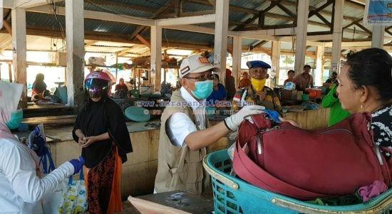 Bupati Tafdil saat membagikan masker kepada pedagang dan pengujung pasar