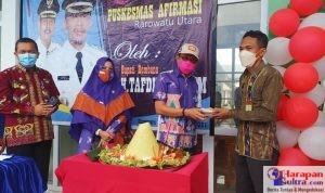 Bupati Bombana, H. Tafdil saat menyerahkan tumpeng kepada Kepala Puskesmas Rarowatu Utara Satar, SKM